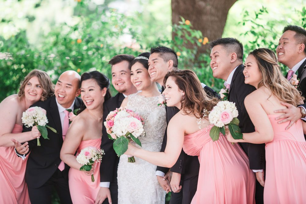 Fun candid photo of the wedding party wearing pink bridesmaid dresses captured by top Orlando wedding photographers