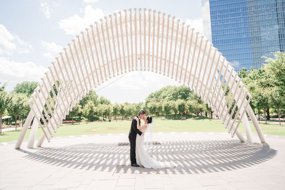 Portrait of the bride and groom in front of a sculpture at Myriad Gardens in Oklahoma City captured by traveling photographers