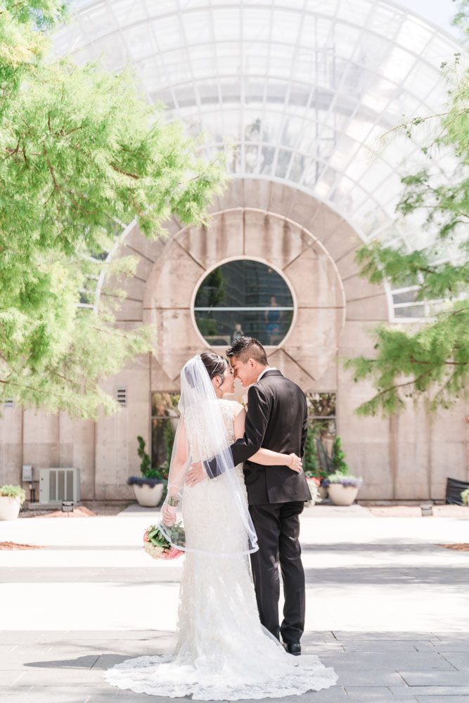 Portrait of the bride and groom in front of a building at Myriad Gardens in Oklahoma City captured by traveling photographers