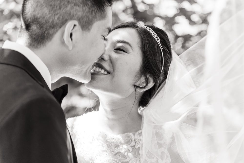 Black and white portrait of Asian bride and groom under veil captured by top Orlando wedding photographer