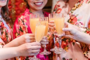 Bride and bridesmaids share a toast during wedding day preparation