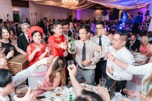 Chinese bride and Vietnamese groom share a toast with their guests at Hy Palace wedding in Oklahoma captured by traveling photographers from Orlando
