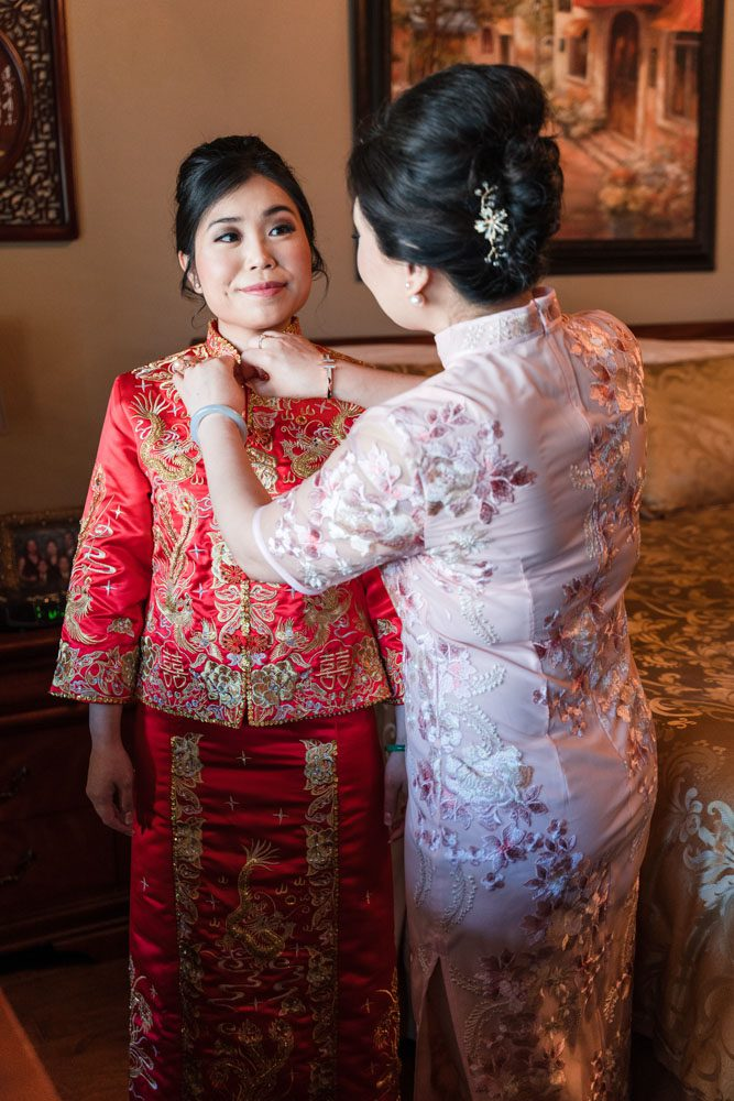 Brides mom helps her with traditional chinese wedding attire during her Asian wedding in Oklahoma City