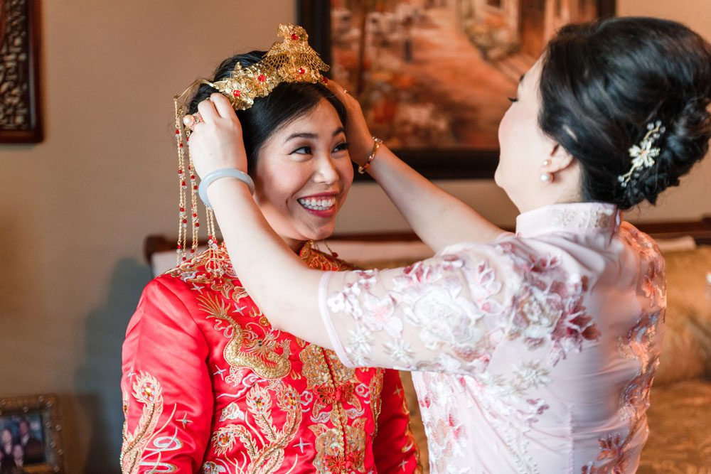Brides mom helps her with traditional chinese headpiece during her Asian wedding in Oklahoma City