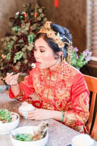 Chinese bride eats her traditional breakfast with chopsticks during her Asian wedding in Oklahoma City captured by Orlando wedding photographer