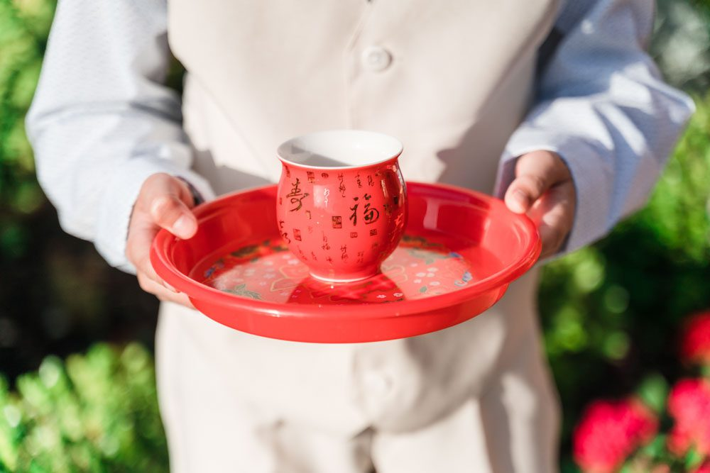 Boy serving tea for a chinese and vietnamese tea ceremony at a wedding in Oklahoma City captured by top Orlando wedding photographers