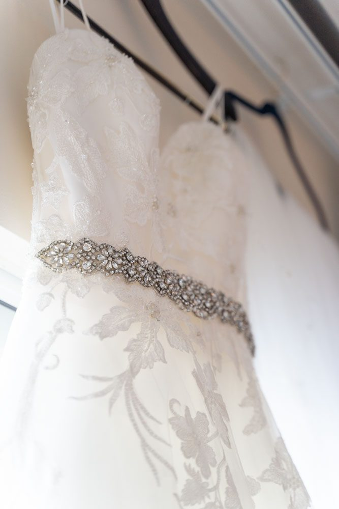 Brides dress hanging in the window during wedding day preparation for her Orlando wedding