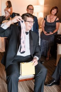 Groom opens a fun gift from the bride of socks with her face during their Orlando wedding day