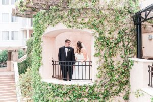 Beautiful and romantic portrait of bride and groom standing at a balcony during their wedding in Orlando Florida
