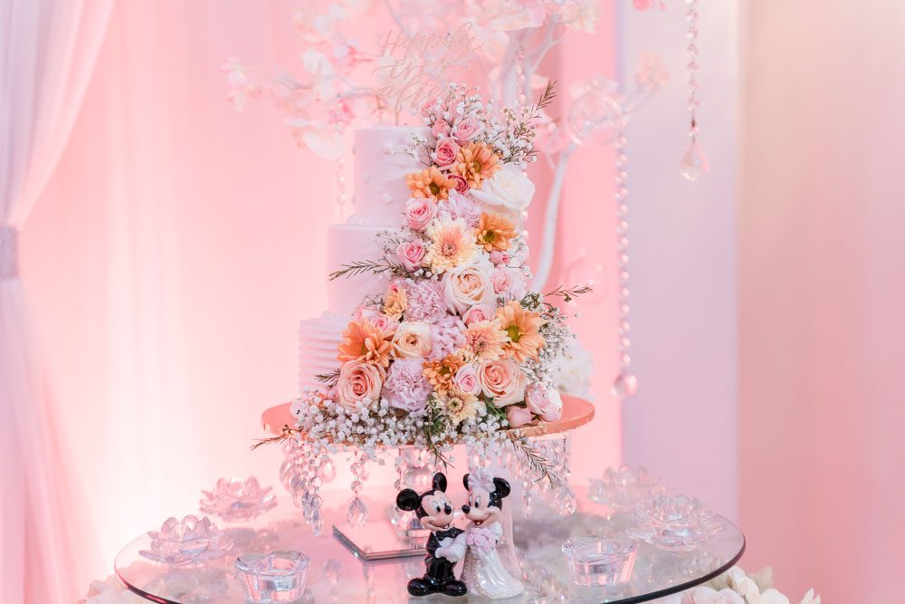 Beautiful white wedding cake covered in fresh flowers during Orlando wedding at the Crystal Ballroom