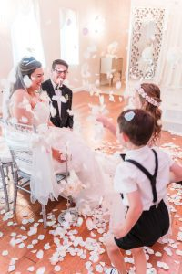Flower girl and ring bearer throw rose petals at the bride and groom at the Crystal Ballroom wedding venue in Orlando