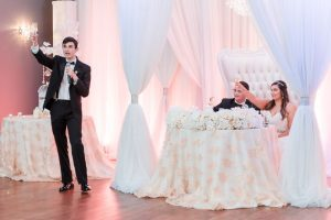 Couple receives a toast at their wedding reception at the Crystal Ballroom veranda captured by Orlando wedding photographer and videographer