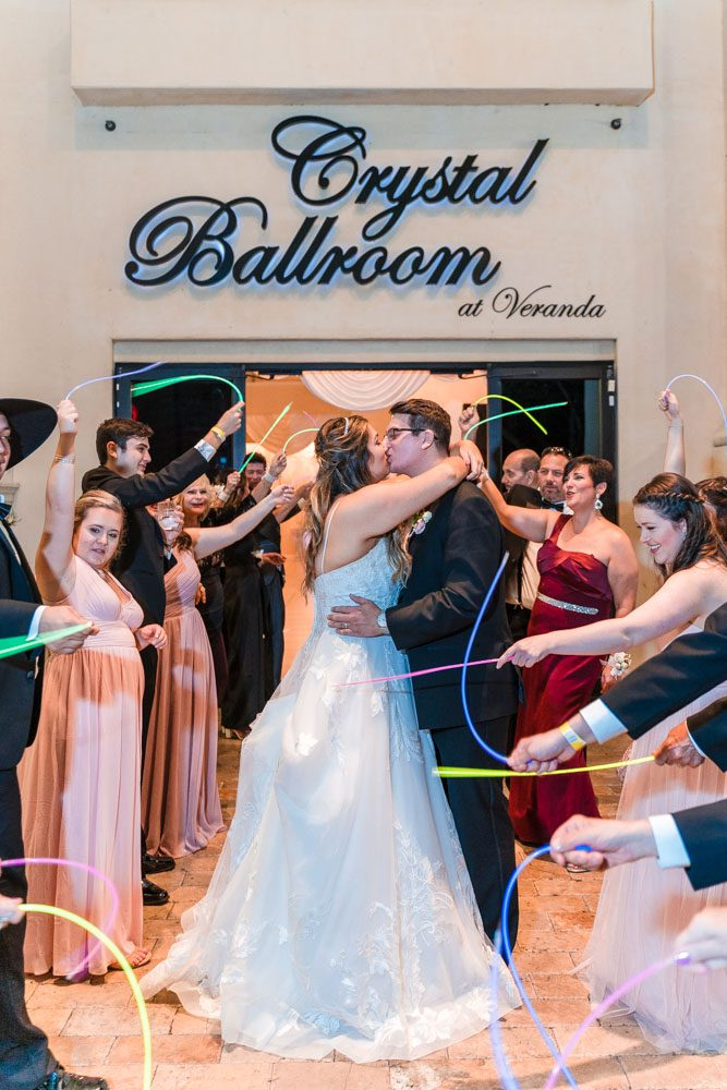 Couple has a grand exit with glow sticks at the Crystal Ballroom wedding venue in Orlando, Florida
