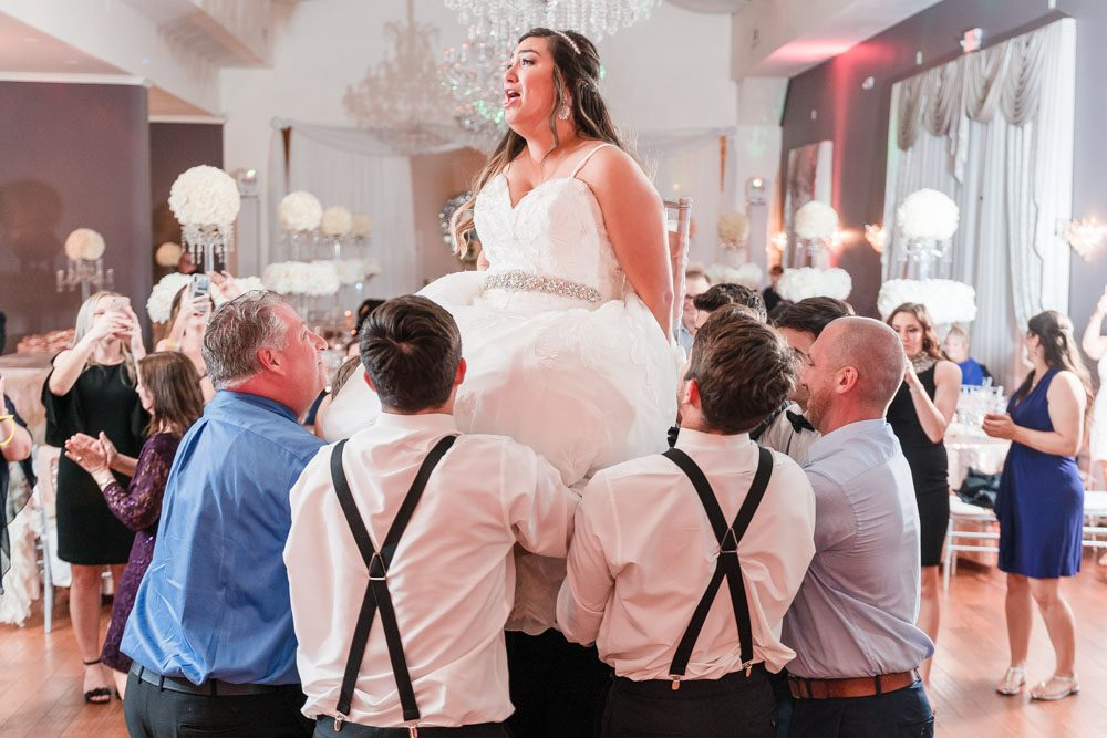 Bride being lifted for the Jewish tradition the hora during their Orlando wedding reception at the Crystal Ballroom