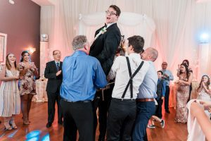 Groom being lifted for the Jewish tradition the hora during their Orlando wedding reception at the Crystal Ballroom